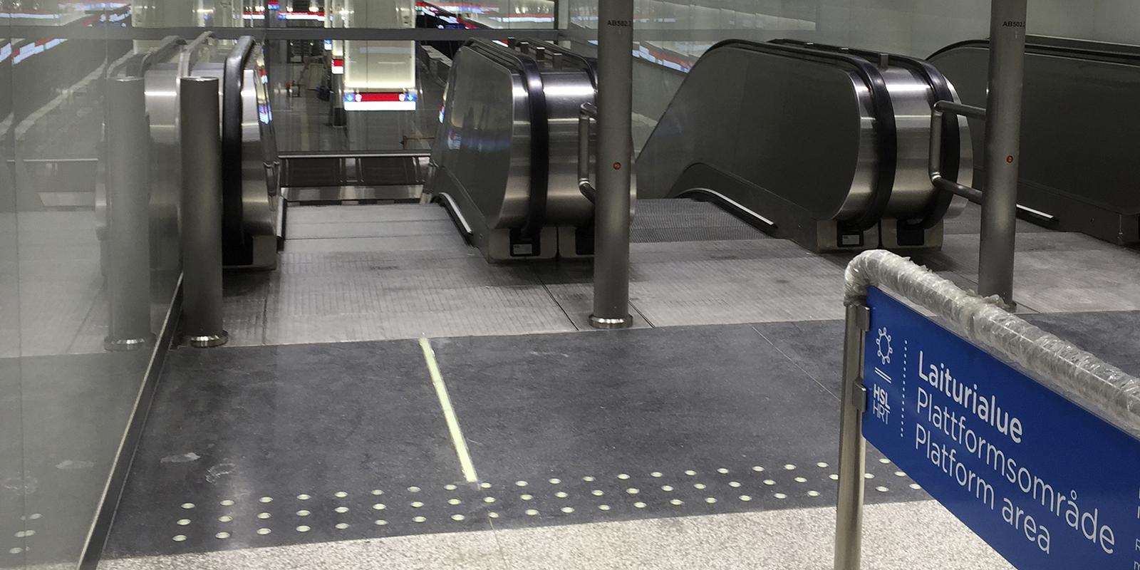 Jälkihohtava lattiaopaste ohjaa näkövammaisia liukuportaisiin.