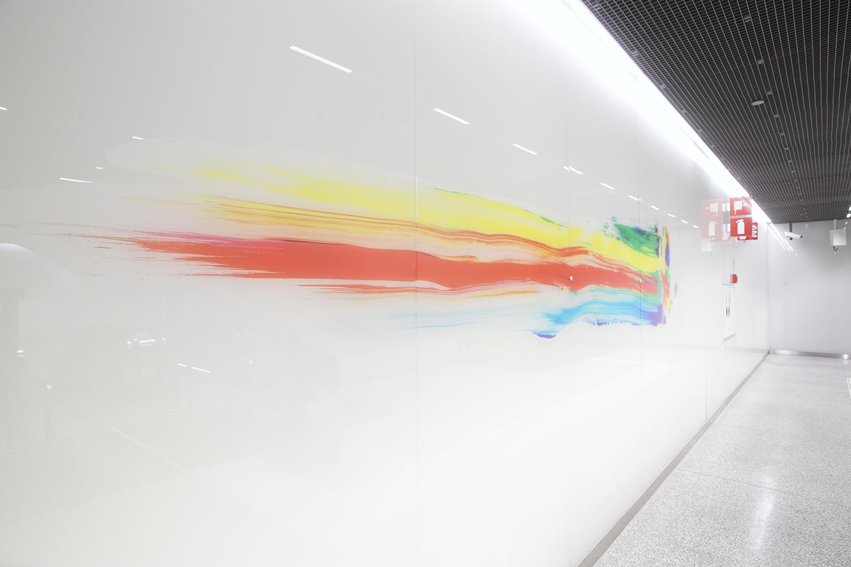 Emma jättää jäljen -taideteoksen osana on värikkäät jäljet valkoisessa seinässä.
