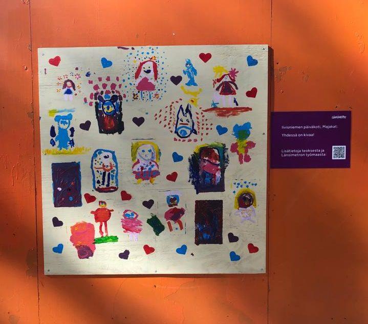 Lasten maalauksessa on ihmisiä eriväristen sydänten keskellä.