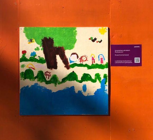 Lasten maalauksessa on puu, ihmisiä ja eläimiä veden äärellä.