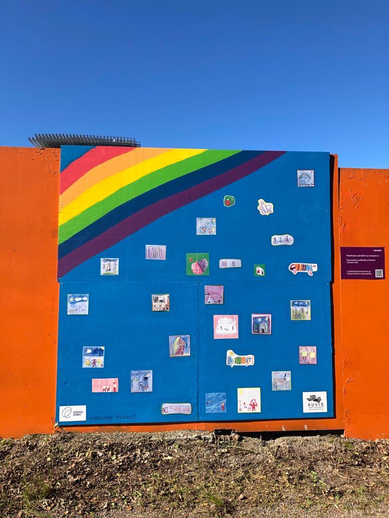 Lasten teoksessa on sateenkaari, jonka alla useita pienenmpiä piirustuksia sinisellä taustalla.