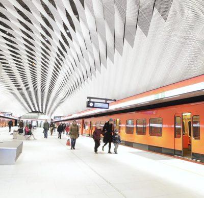 Kuvassa on Matinkylän metroaseman metrolaituri. Metro on pysähtynyt asemalle. Laiturilla on ihmisiä. Laiturin katto koostuu valkoisista alumiinilevyistä.