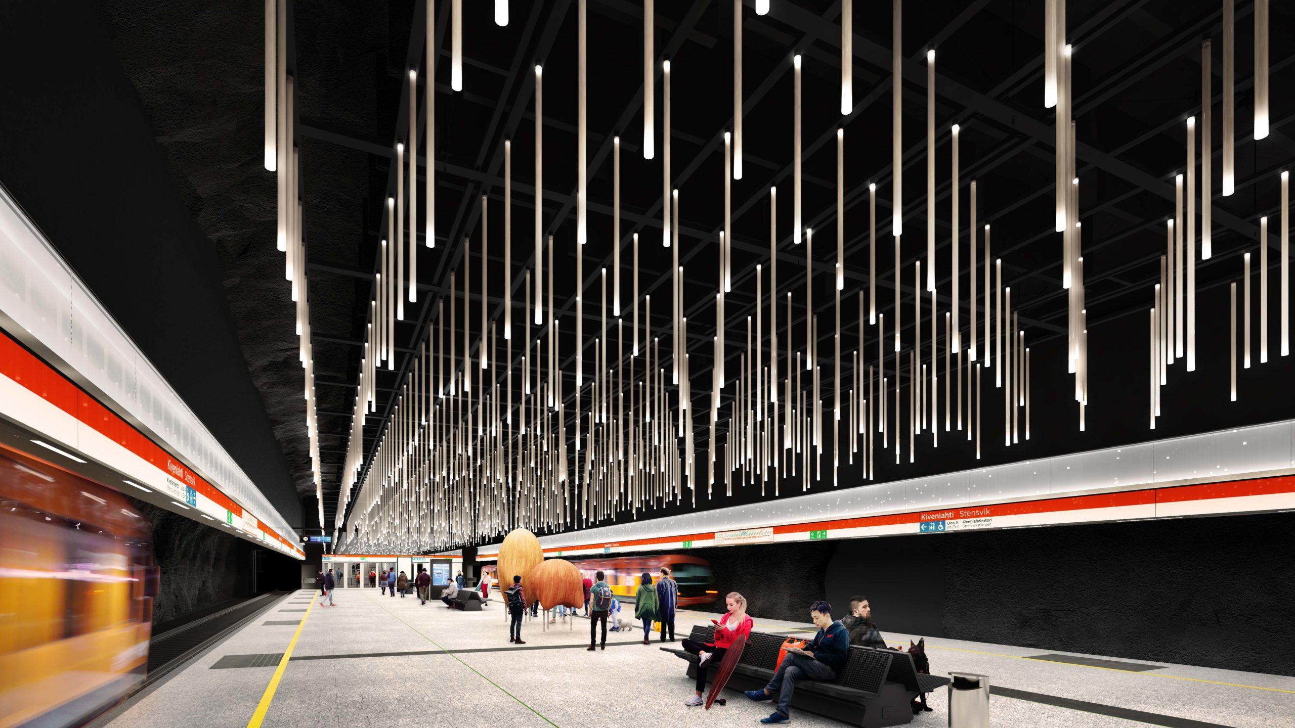 Havainnekuva tulevan Kivenlahden metroaseman metrolaiturilta. Laiturin katosta riippuu useita valaisimia. Laiturilla näkyy kaksi oranssia veistosta. Veistos on nimeltään Kulkijat.