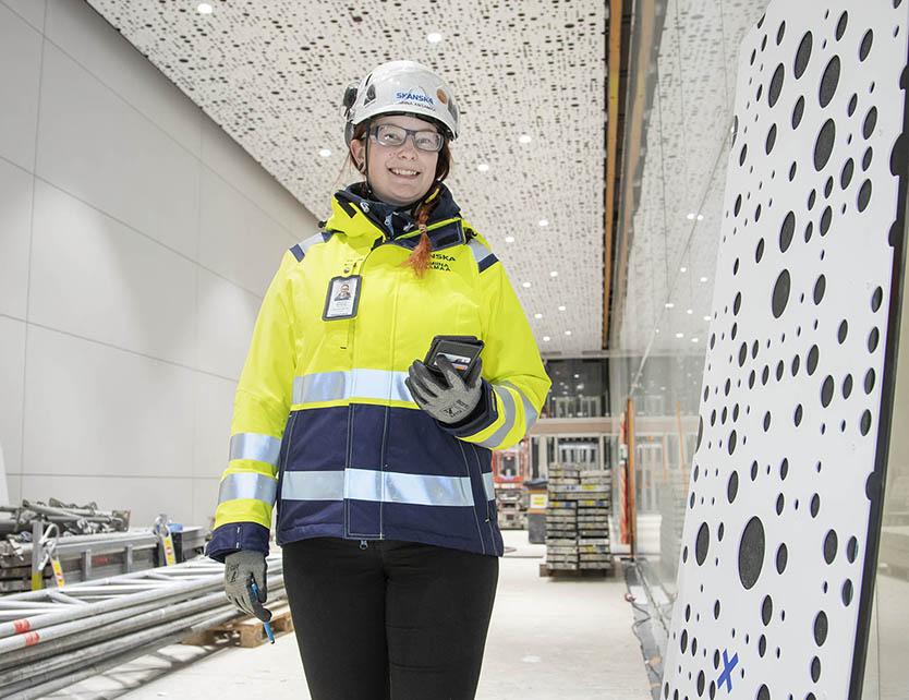 Työmaavarusteisiin pukeutunut nainen seisoo metrotyömaalla Kivenlahden metroasemalla.