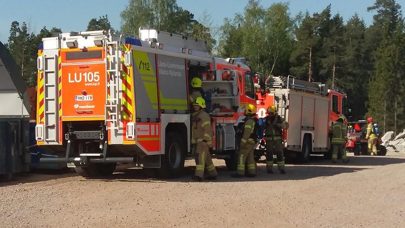 Kuvassa on paloauto ja palomiehiä.