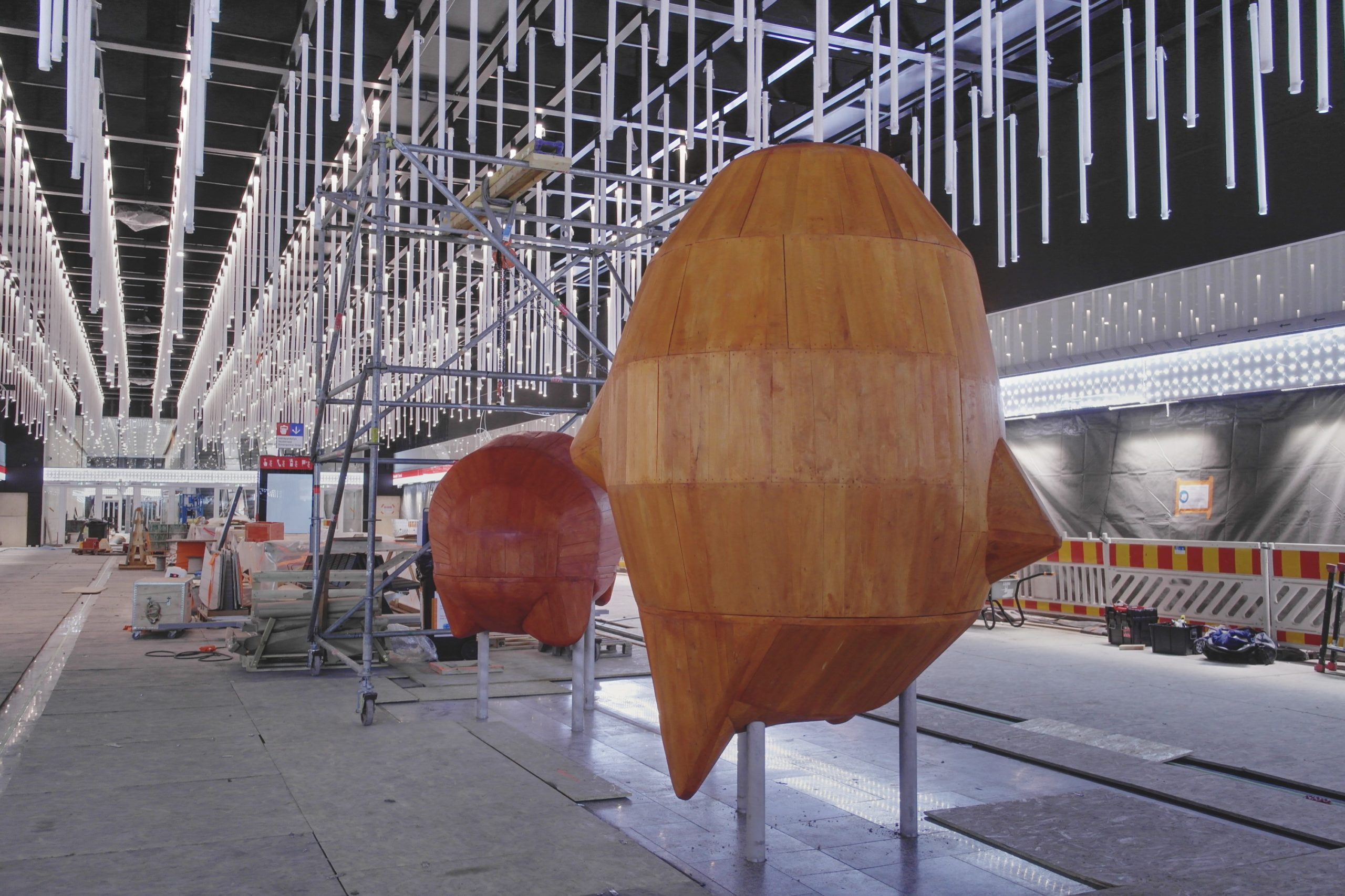 Kuvassa näkyy kaksi oranssia hahmoa metrolaiturilla, joka on vielä työmaa.