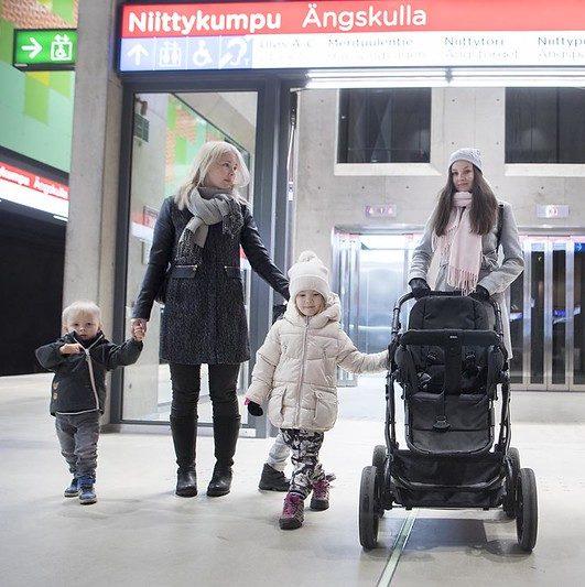 Kuvassa on kaksi naista ja kolme lasta metroasemalla lastenrattaiden kanssa. Taustalla näkyy metroaseman opasteet.