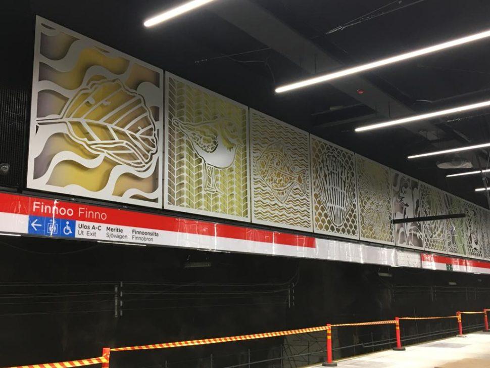 Kuvassa näkyy asemalaiturin seinää, jossa värikkäitä luontoaiheisia kuvia. Kuvissa on mm. lehti, lintu, kala ja simpukka.