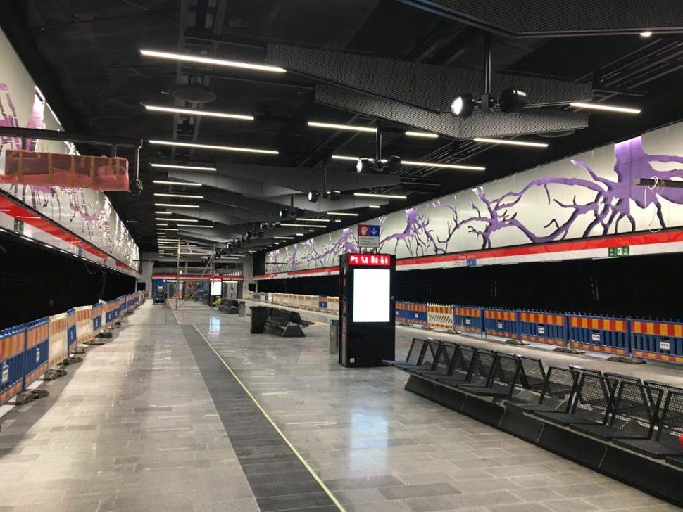 Kuvassa on Kaitaan metroaseman asemalaituria. Asemalaiturin seinässä näkyy violetteja puun juuria valkoisella taustalla.