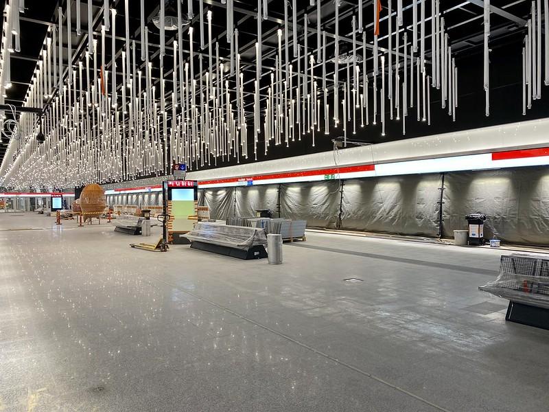 Kuva Kivenlahden metroaseman asemalaiturilta. Katossa on roikkuvia pitkiä valaisimia. Asemalaiturilla on oranssi veistospari, Kulkijat.