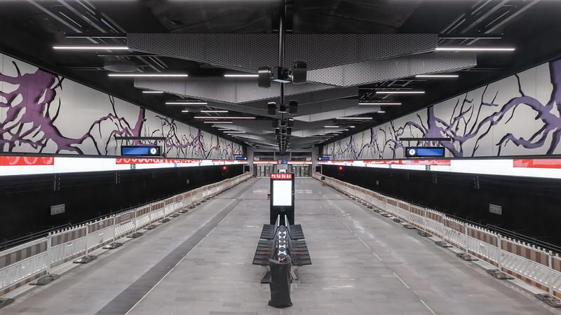 """Kuvassa on Kaitaan metroaseman asemalaituri. Asemalaiturin seinillä näkyy Antti Tantun """"Juurtuminen""""-teos, jossa on puun juuristo kulkee koko asemalaiturin mitan. talta"""