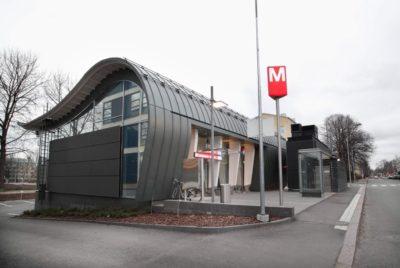 Metrotunnus seisoo sisäänkäyntirakennuksen edessä.