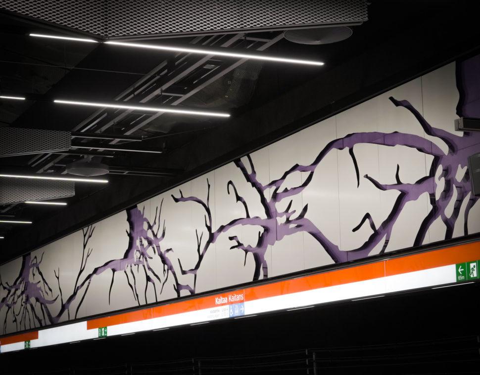 Valkoisen seinälevyn aukoista näkyy violettia taustalevyä, joka muodastaa juurien verkoston metroaseman laiturialueen seinään. Metroasema on Kaitaa.
