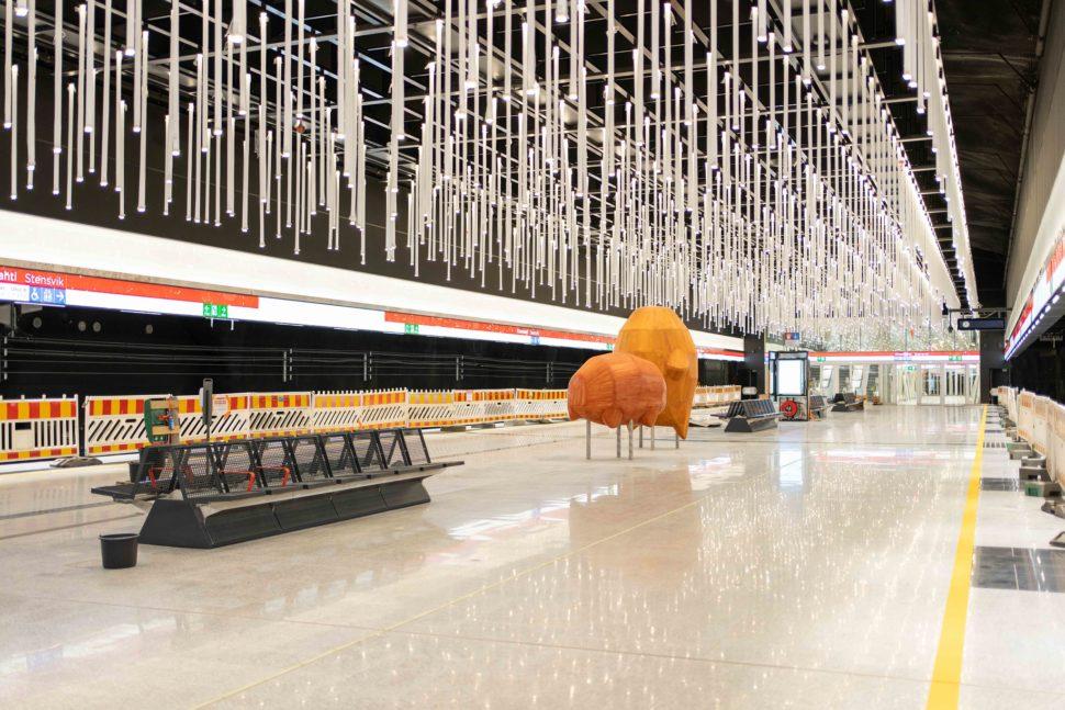 Oranssit puuveistokset valoisalla metrolaiturilla, Laiturialueen katossa on lukuisia roikkuvia valaisimia.
