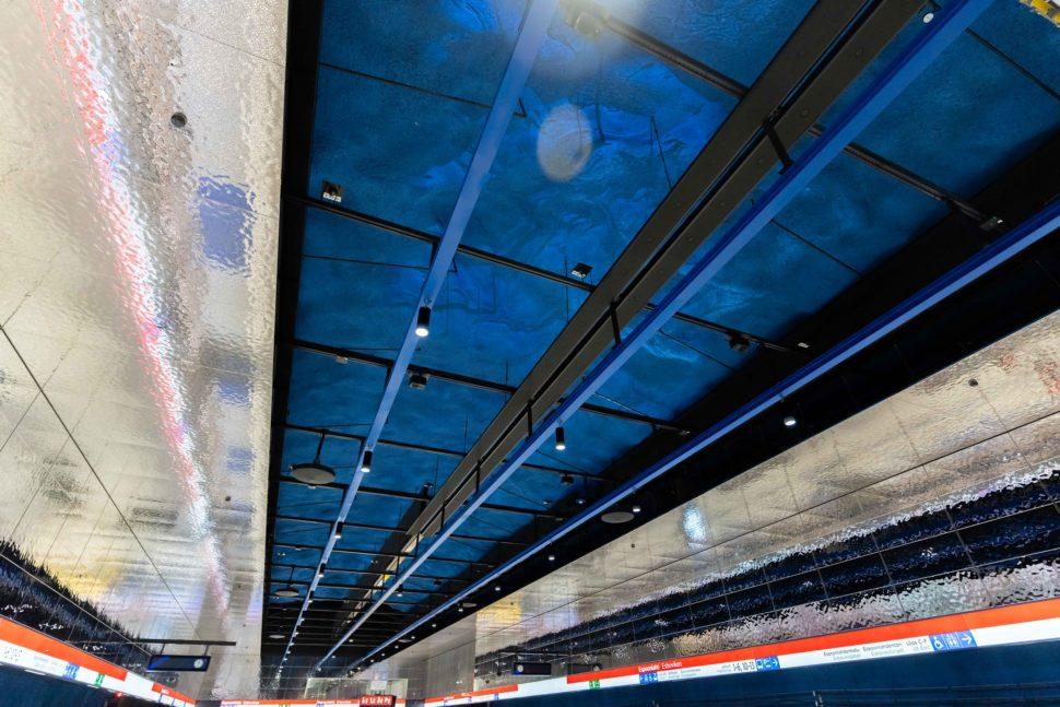 Metrolaiturin sinisessä katossa on valokuvioita. Asemalaiturin seinät ovat kiiltävät kromiseinät. Asema on Espoonlahden metroasema.