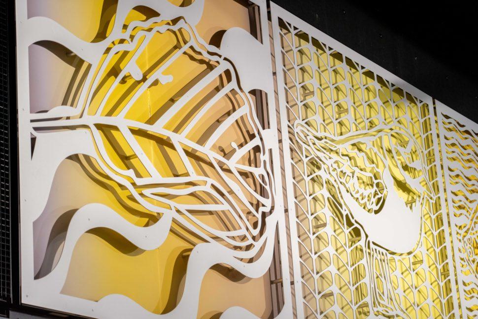 Taideteoksessa on neliönmuotoisia kuvioita, joiden taustalla on värikäs taustalevy. Kuvioissa on lehti ja lintu.