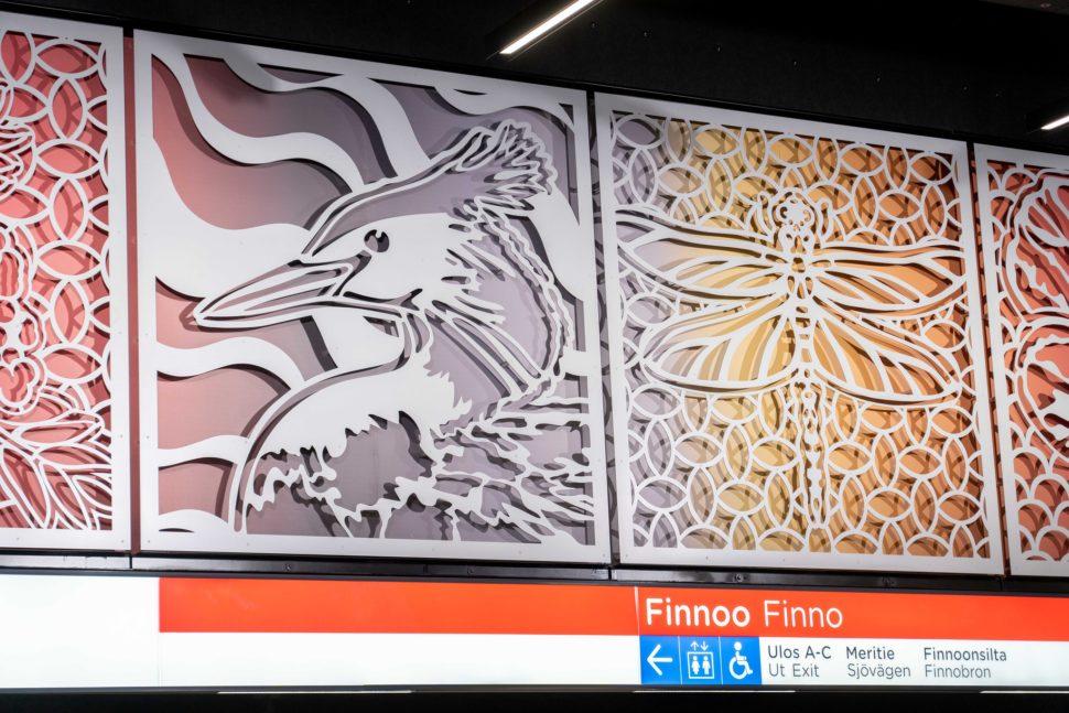 Metroaseman seinässä on neliönmuotoisia kuvioita, joita taustalla on värikäs tausta. Kuvioissa on lintu ja sudenkorento. Metroasema on Finnoo.